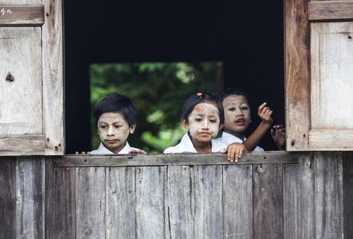 Escolares. Los niños de Maukkadaw asisten a una escuela construida en teca, madera de la que vive el pueblo. Visten un uniforme blanco y verde y llevan la cara cubierta con thanaka, una pasta extraída de la corteza de este árbol. Esta crema les protege del sol y cuida su piel.