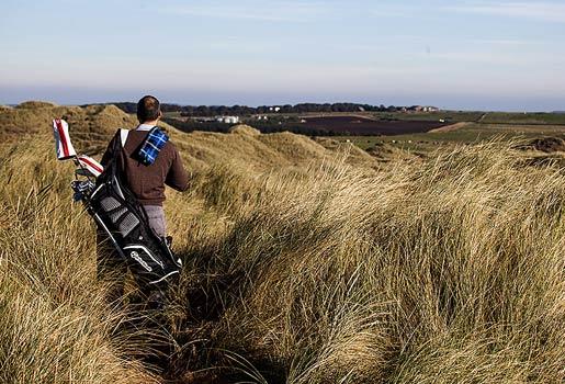 Entorno salvaje. Un jugador de golf atraviesa las dunas para acceder al Trump International.