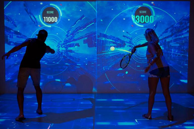 Dos visitantes juegan en el simulador del Rafa Nadal Museum Xperience, uno de los espacios del complejo.